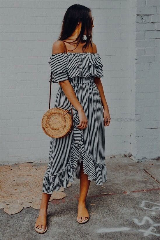 a striped ruffled off the shoulder dress with a front slit, tan flats and a round wicker bag