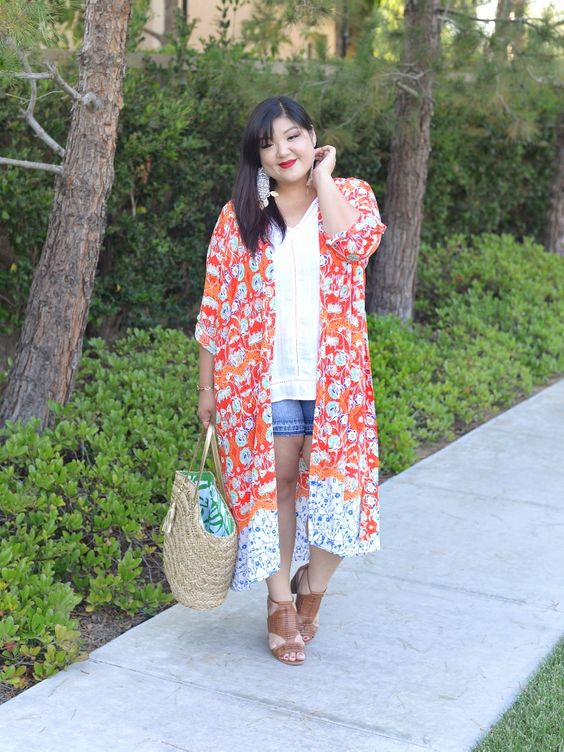 a white top, denim shorts, a bright floral kimono, brown heels and a straw bag for a holiday look