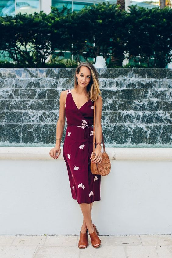 a plum-colored wrap dress with a slit, a V-neckline, tan mules and a bag