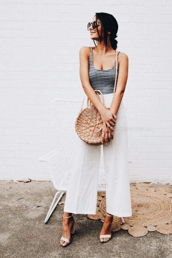 a gingham black and white top, white culottes, white heels and a round wicker bag