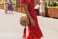 11 a red printed fitting midi dress with a V-neckline, red strappy heels and a straw bag with a tassel