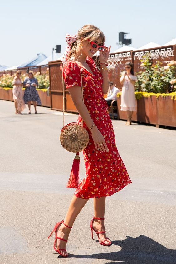 a red printed fitting midi dress with a V neckline, red strappy heels and a straw bag with a tassel