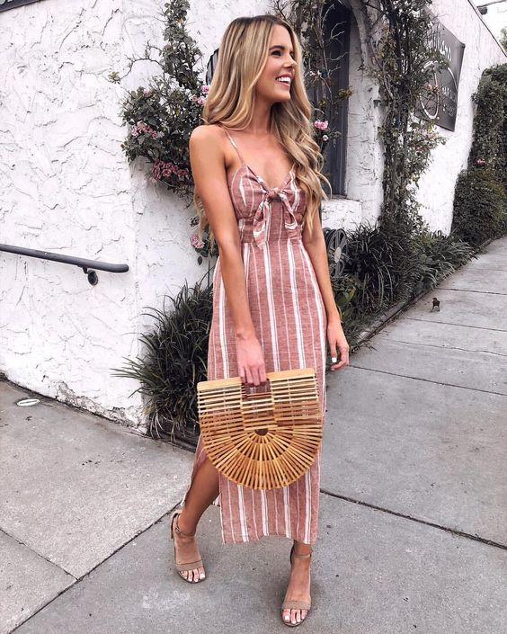 a striped pink and white dress with spaghetti straps, side slits and a bow bodice