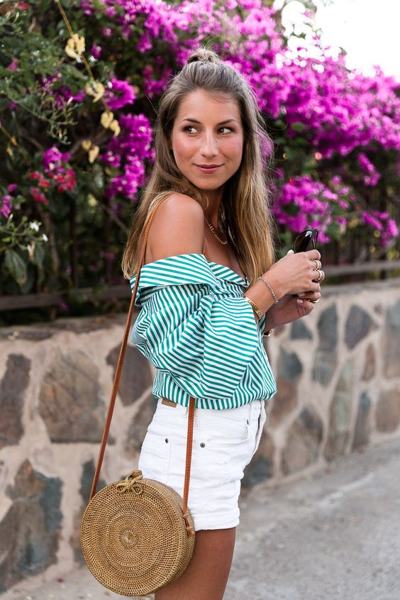 a striped green off the shoulder blouse, white denim shorts, a round wicker bag for a hot day