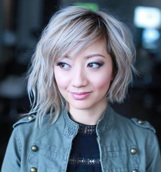 a wavy blonde asymmetrical bob with a black root for a deeper look