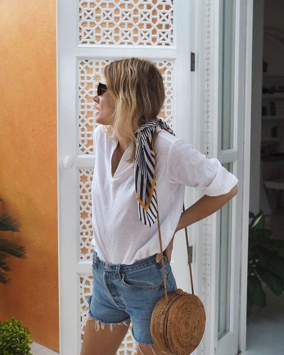 a white shirt, blue denim shorts, a round wicker bag for a casual look