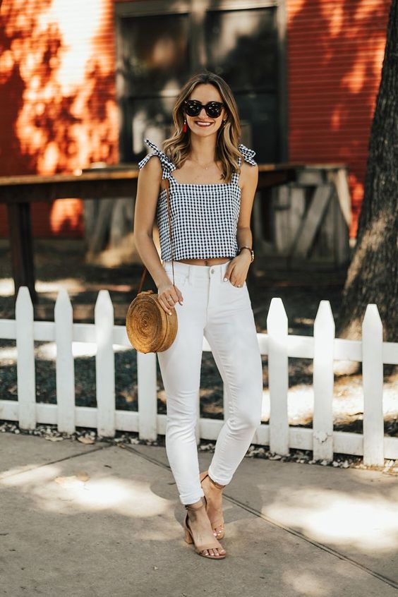 white high waist pants, a gingham top with bows on the shoulder, tan shoes and a round wicker bag