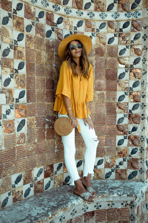 white ripped jeans, a yellow lace up top, polka dot flats, a hat and a round wicker bag