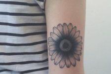 Black daisy tattoo on the hand