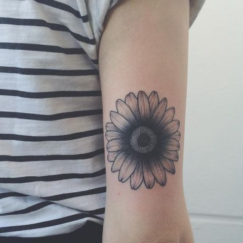 Black daisy tattoo on the hand