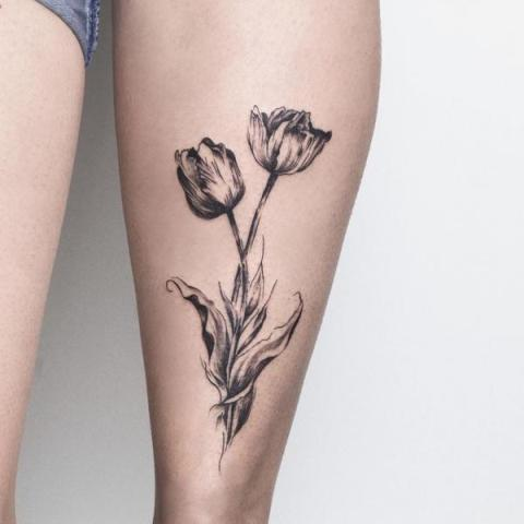 Black tulip tattoo on the leg