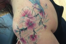 bird tattoo combined with some cherry blossom flowers