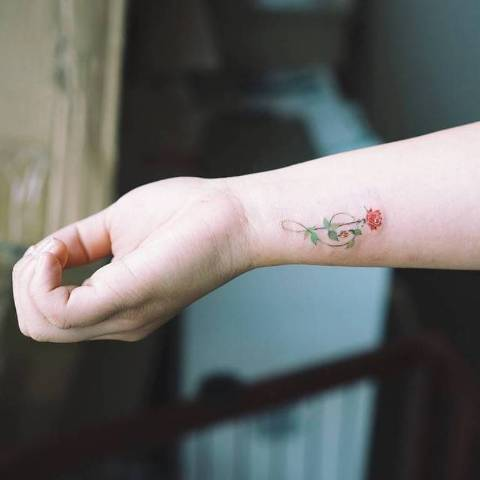 Colorful rose tattoo on the wrist