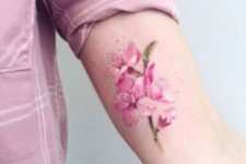 Green and pink tattoo on the arm