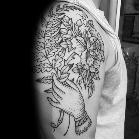 Hand holding flower and fern tattoo