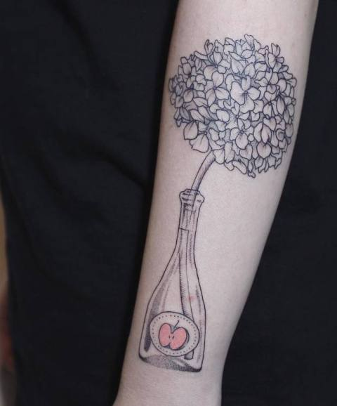 Hydrangea in the bottle tattoo on the arm