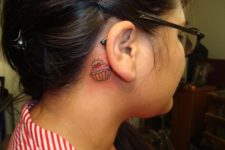 Pink and orange tattoo behind the ear