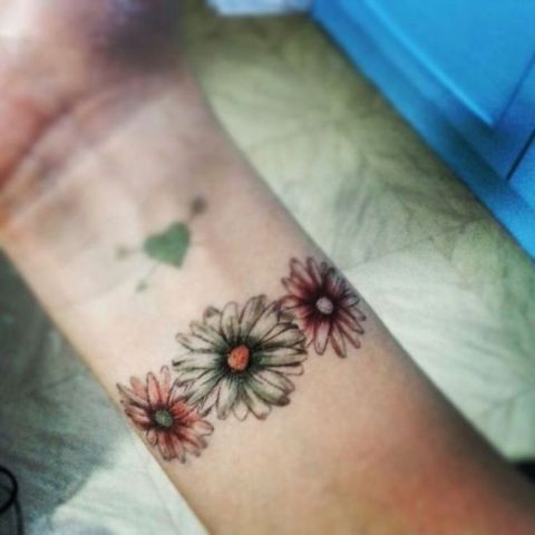 Three flowers tattoo on the wrist