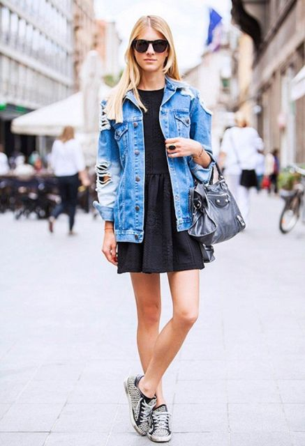 With black mini dress, black bag and printed sneakers