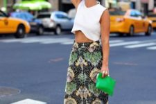With white crop top, green clutch and white and black shoes
