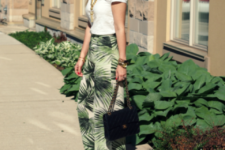 With white t-shirt, black bag and heels