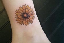 Yellow sunflower tattoo on the leg