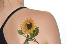 Yellow sunflower with green leaves tattoo