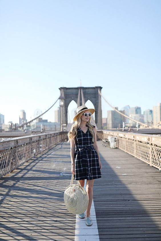 a black and white plaid sleeveless short dress, a hat, a straw bag and silver shoes