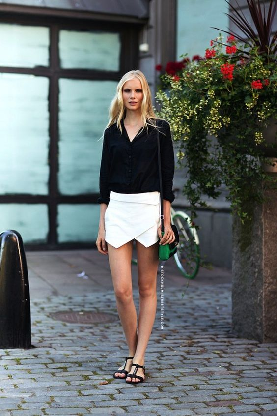 a black shirt, a white asymmetrical mini skirt, black sandals and a colorful  bag