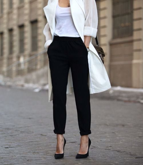 a minimalist outfit with black pants and shoes and a white tee and duster