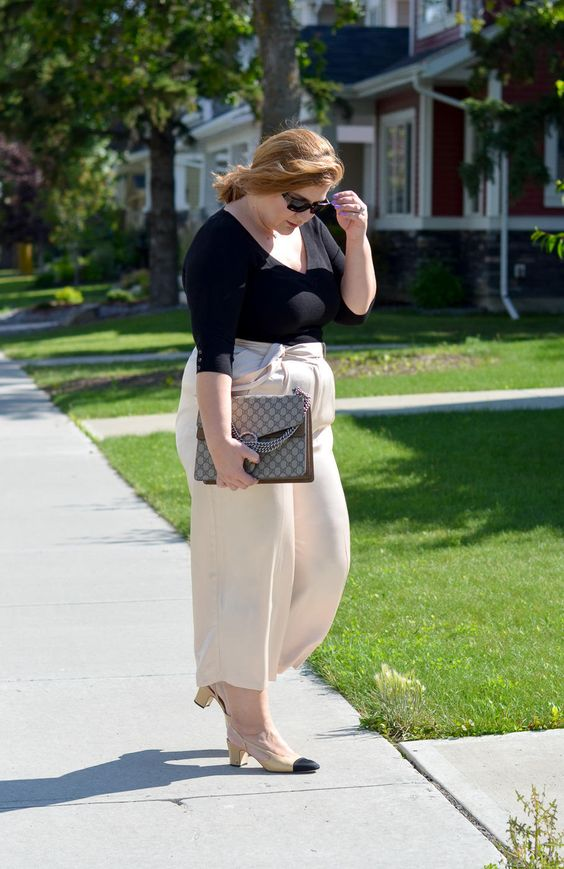 a black long sleeve top, creamy culottes, cream and black shoes and a large bag
