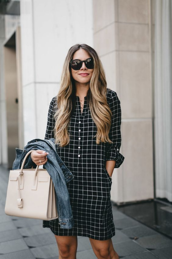 a black plaid shirtdress with buttons, a denim jacket, a black bag for a casual look
