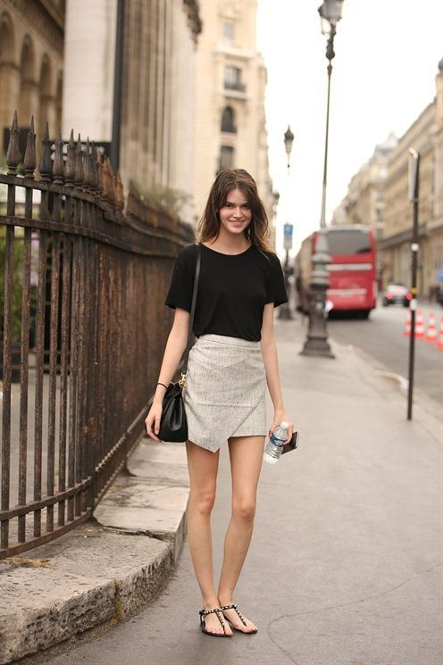 a black tee, a grey symmetrical skirt, black sandals and a black bag for a hot day