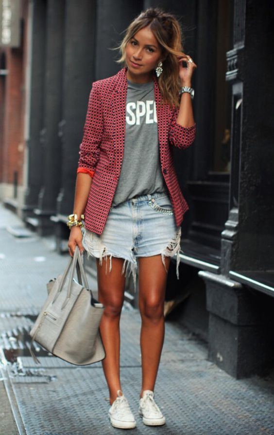 a grey printed tee, a red printed jacket, denim shorts, white sneakers and a grey bag