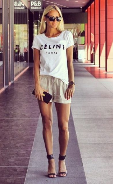 a white Celine t-shirt, neutral shorts, black strappy heels and a tiny clutch