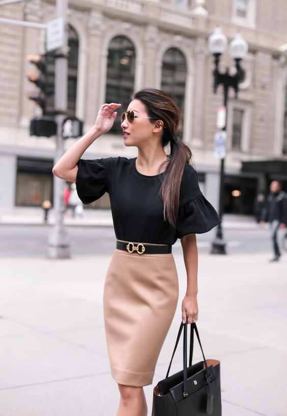 a camel pencil skirt, a black shirt with ruffled short sleeves and a blaack bag