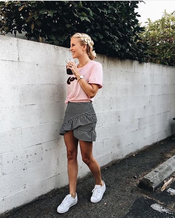 a pink logo t-shirt, a gingham black and white ruffled asymmetrical skirt, white sneakers
