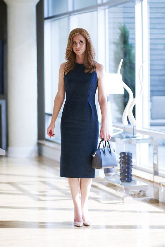 a sheath navy dress without sleeves and with side piping to highlight the waist