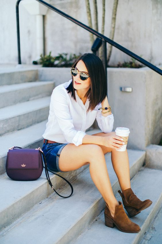 a white shirt, blue denim shorts, brown suede booties and a purple bag