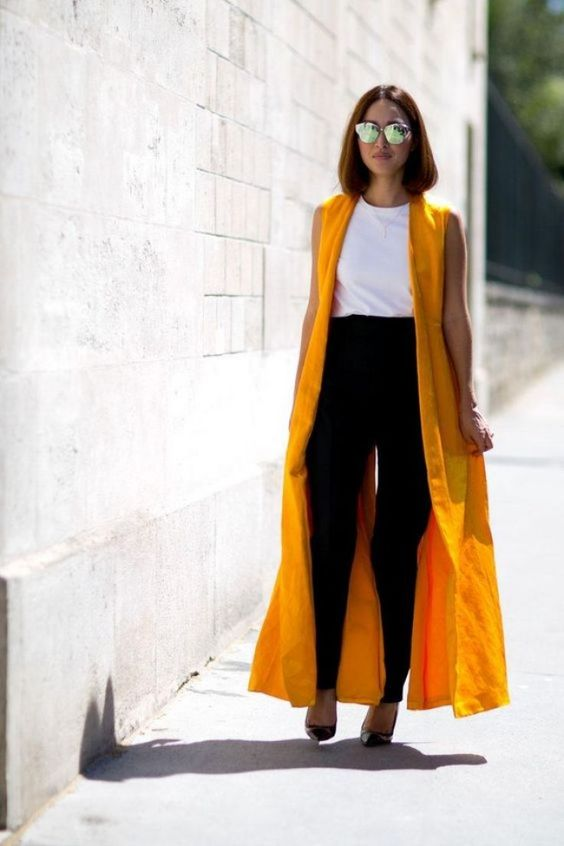 a white tee, black pants and shoes plus a yellow duster vest to add color