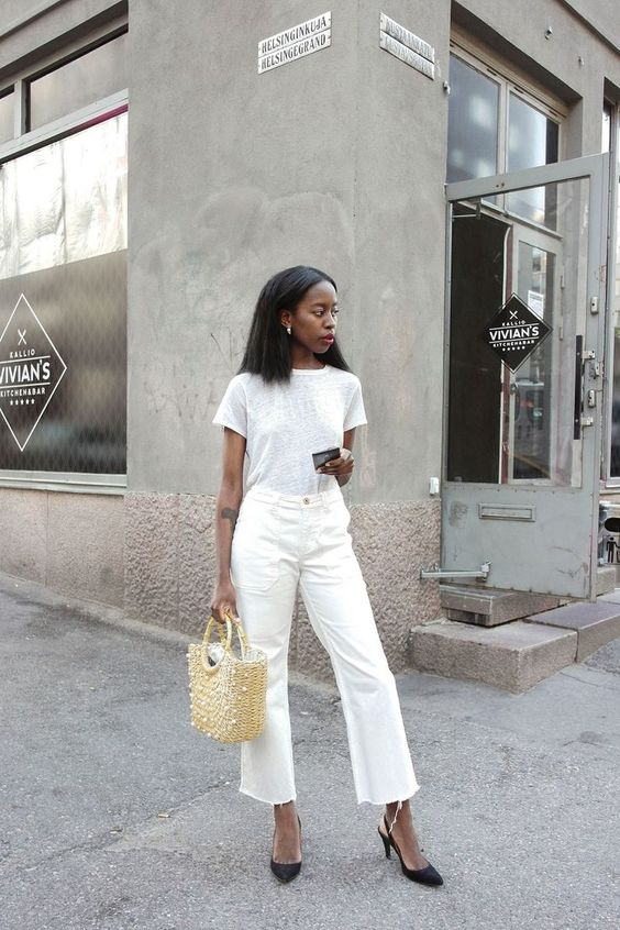a white tee, white cropped jeans with a raw hem, black heels and a straw bag