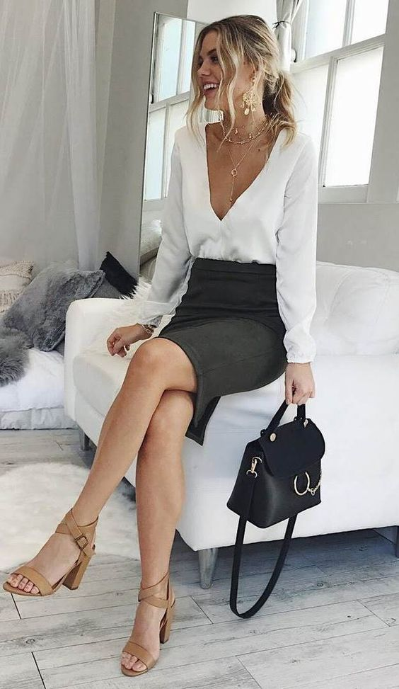 a black pencil skirt and a white blouse with a deep neckline plus layered necklaces that highlight it