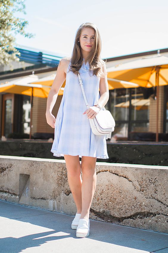 a blue sleeveless knee plaid dress, white sneakers and a white bag for a cool look