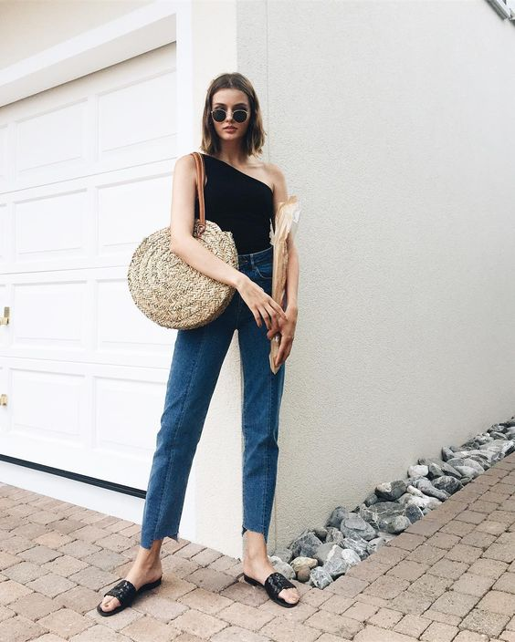 blue cropped jeans with a raw edge, a black one shoulder top, bblack slippers and a straw bag