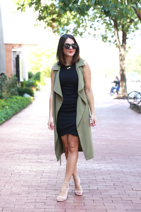 a black bodycon dress with an asymmetrical skirt, an olive green duster vest and metallic shoes