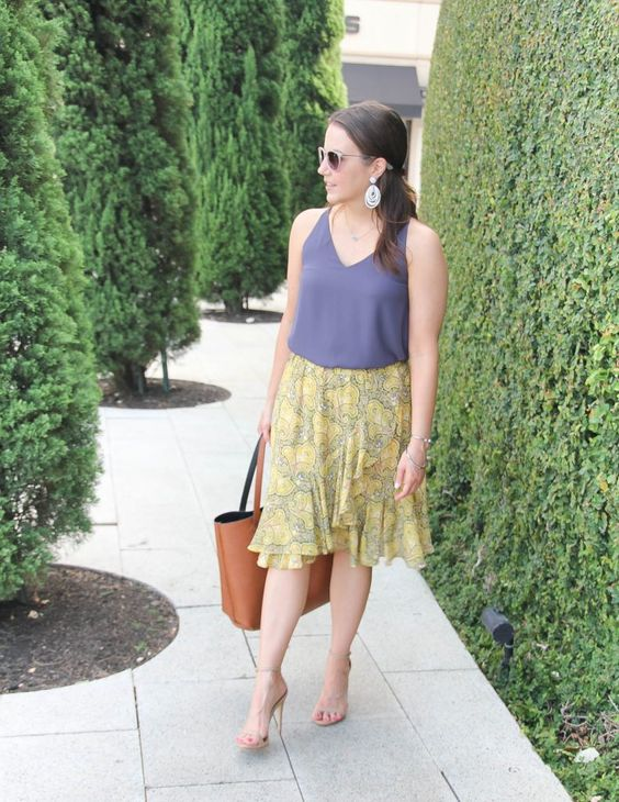 a casual work look with a blue strap top and a yellow printed ruffled skirt, nude heels and an orange bag