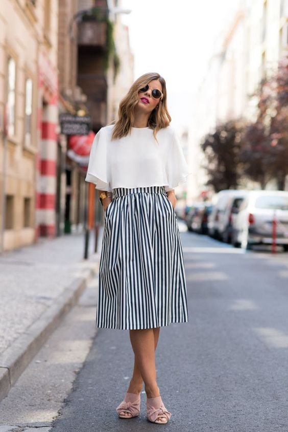 a striped navy and white midi skirt, a white crop top, blush tie mules for a trendy touch