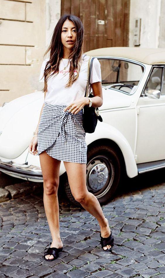 a white tee, a gingham mini asymmetrical skirt, black slippers and a bag