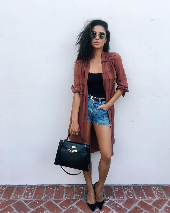 blue denim shorts, a black spaghetti strap top, black heels, a rust duster and a black bag