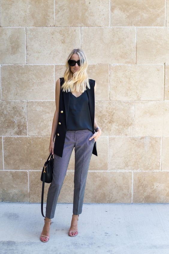 printed purple pants, a black top, a black duster vest and nude shoes plus a bag